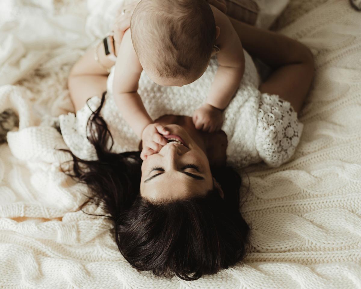 yatakta uzanmış anne ve bebeğin beraber etkileşimi